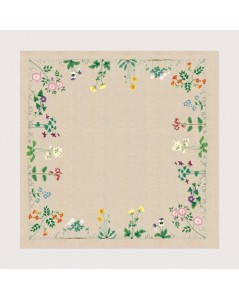 Linen tablecloth with flowers stitched along the perimeter of the tablecloth by traditional stitch